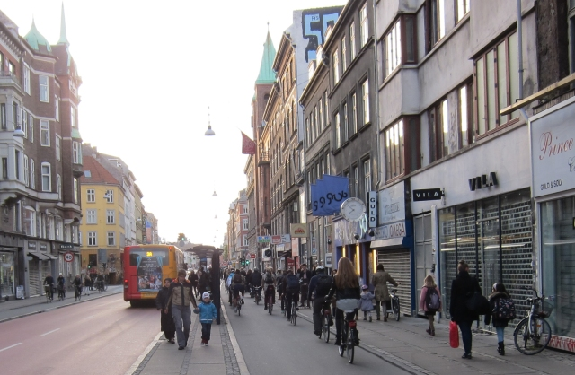 "Bicyclists, pedestrians, and buses line Norrebrogade, which utilizes ""Green Wave"" signal timing to promote efficient bicycle flow."