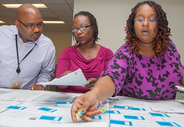 DDOT's Anthony Foster, Joanne Bassett-Lowe, and Angelica Johnson process a table full of School Transit Subsidy Program applications.