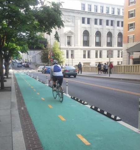 Green paint and long dividers help protect bicyclists on DDOT's new First Street NE protected bike lane.