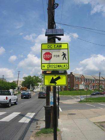 A pedestrian beacon features flashing lights to warn motorists to look out for pedestrians.
